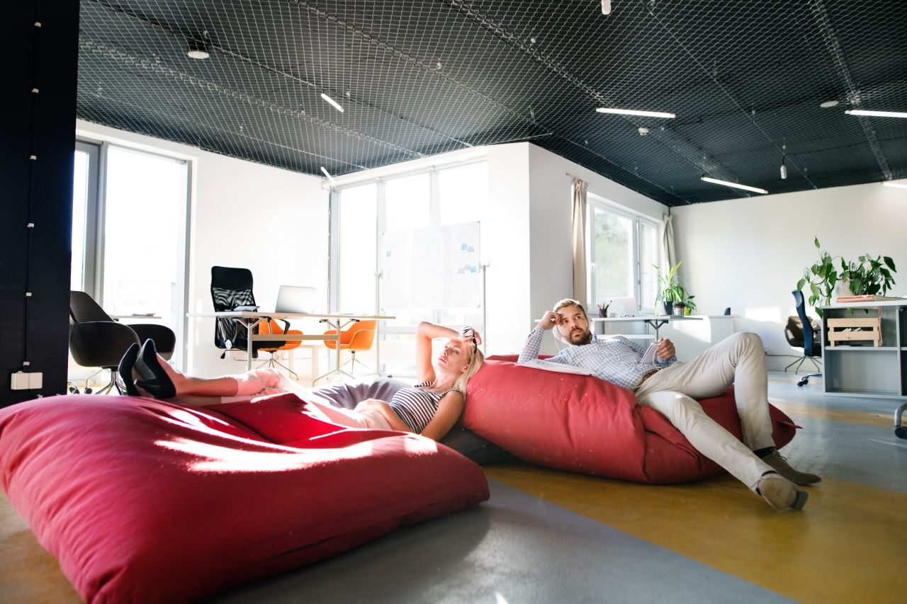 Business people in the office sitting in bean bags.